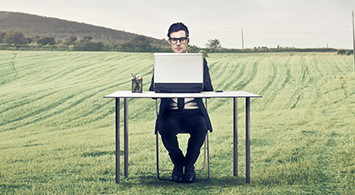 businessman working on computer in natural landscape