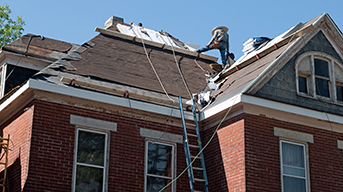 Man standing on a roof and repairing old construction