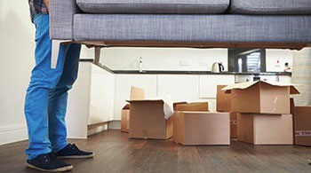 Man carrying sofa when he moves into new home